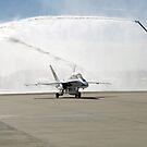 Ein F-18 Flugzeug rollt unter dem Spray von Feuerwehrautos. von StocktrekImages