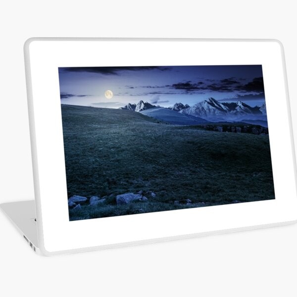 meadow with huge stones on top of mountain range at night Laptop Skin