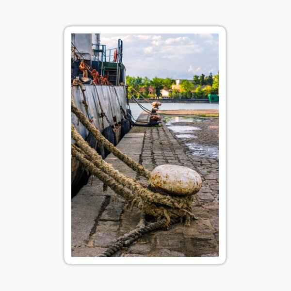 Boat docked to a mooring bollard in the  port of Sozopol at sunset Sticker