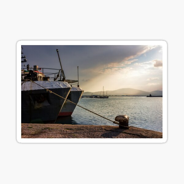 Boats docked to a mooring bollard in the  port of Sozopol at sunset Sticker