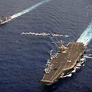 F / A-18 Hornets fliegen in Formation über USS Abraham Lincoln und USS Cape St. George. von StocktrekImages