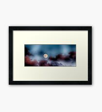 The moon in the clouds at sunset Framed Print