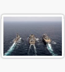 Military ships conduct an underway replenishment in the Pacific Ocean. Sticker