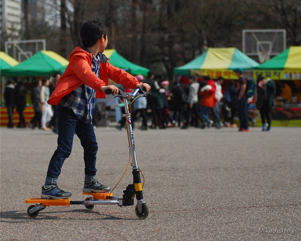 Korean Boy on a 3 Wheeled Scooter (1) by Mike Ashley