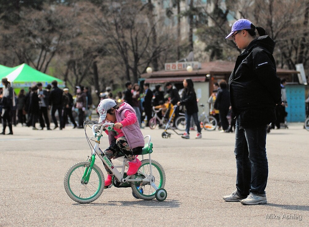 Mom Teaching Daughter to Ride a Bike by Mike Ashley