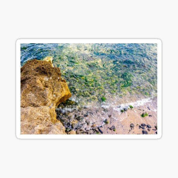 wave rolls onto the rocks of sandy coast Sticker