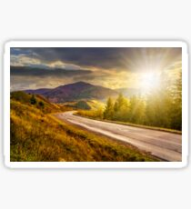 mountain road near the coniferous forest with cloudy sky at sunset Sticker