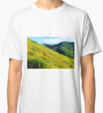 yellow poppy flower field with green leaf and green mountain and cloudy blue sky in summer Classic T-Shirt