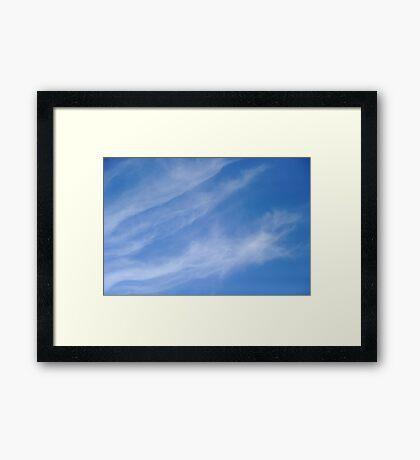 Wispy white clouds on blue sky Framed Print