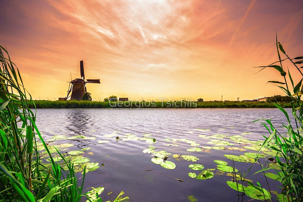Traditional village with dutch windmills and river at sunset, Holland, Netherlands. by Georgios Tsichlis