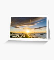 Golden hour sunset over beach at low tide with rocks in the foreground Greeting Card
