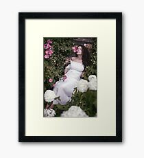 Romantic portrait of a woman smelling roses lying on stairs in a garden art print Framed Print