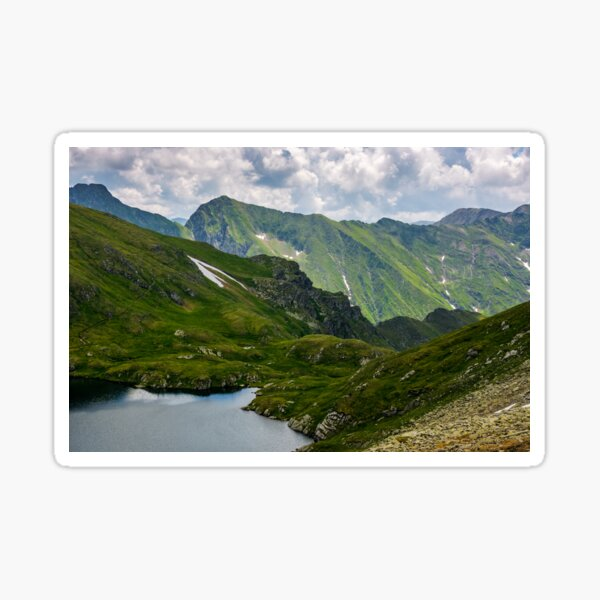 lake in mountains with snow on hillside Sticker