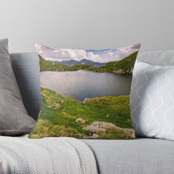 lake in mountains with grass on hillside Throw Pillow