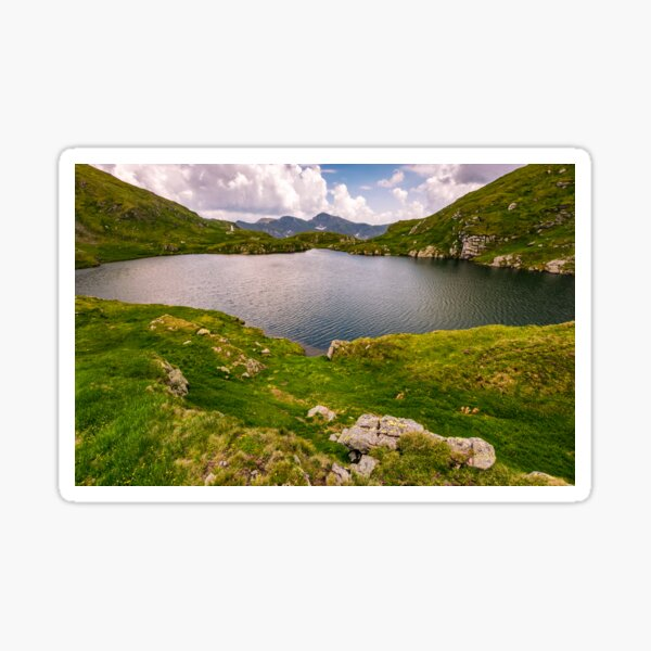 lake in mountains with grass on hillside Sticker