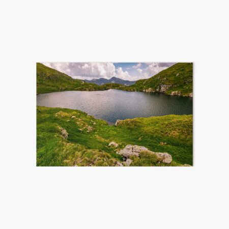 lake in mountains with grass on hillside Art Board Print