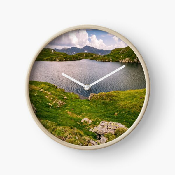 lake in mountains with grass on hillside Clock