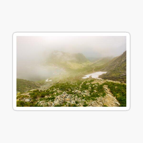 Steep slope on rocky hillside over balea lake in fog Sticker