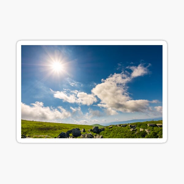 sunburst on a blue sky with clouds over the mountains Sticker