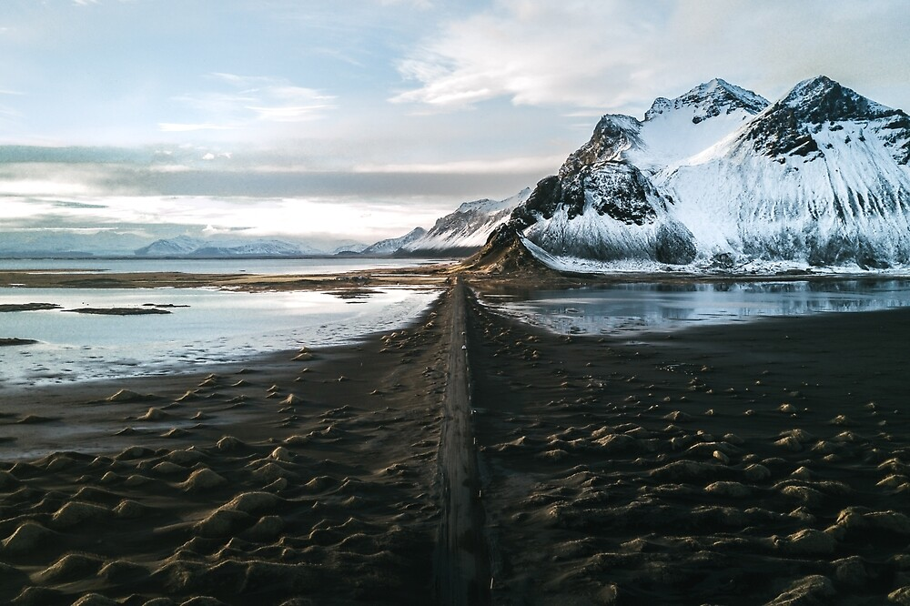 Black sand beach with mountain road in Iceland by Michael Schauer
