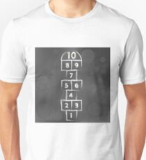 Hopscotch Game on Dark Blurred Background. Symbol of Childhood. T-Shirt