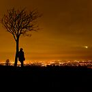 Silhouette of Man Stood By Tree Overlooking Manchester City Centre at Night by Bob Davies