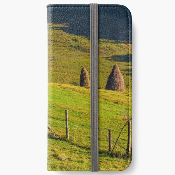 hay stacks behind the fence on rural field iPhone Wallet