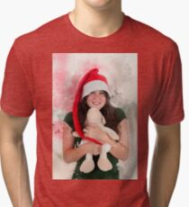 Digitally enhanced image of a Young teen wearing Santa's helper hat and hugging a stuffed Teddy bear with Christmas atmosphere  Tri-blend T-Shirt
