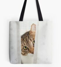 Cat looks out from behind a shower curtain  Tote Bag