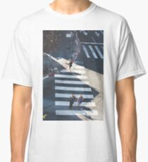 Elevated view of a city crossroads with zebra crossing and pedestrians crossing a street.with large shadows cast by the people.  Classic T-Shirt