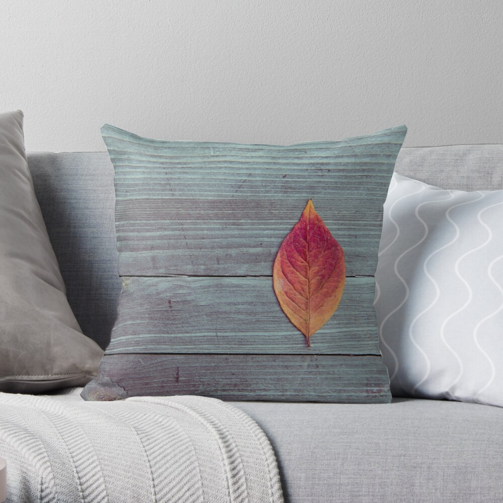 Red autumn leaf on wood Throw Pillow