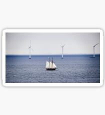 A sailboat in the sea against a background of wind power plants Sticker