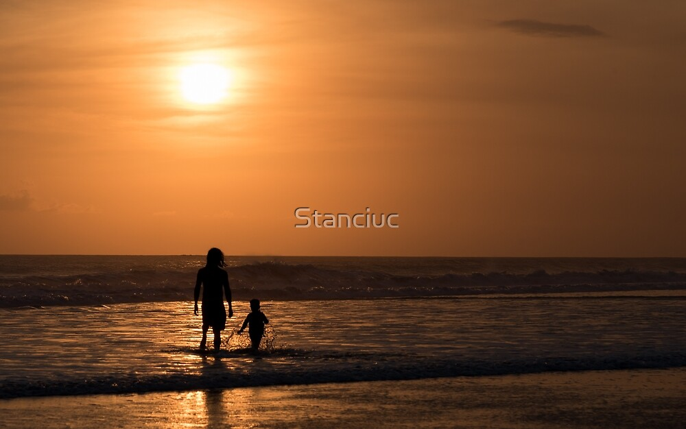 Silhouette of man and child at seaside on sunset by Stanciuc