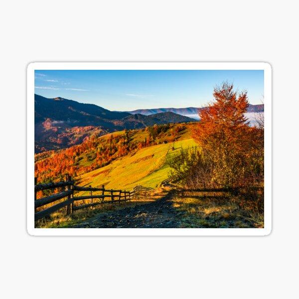 wooden fence through rural fields on hills in fog Sticker