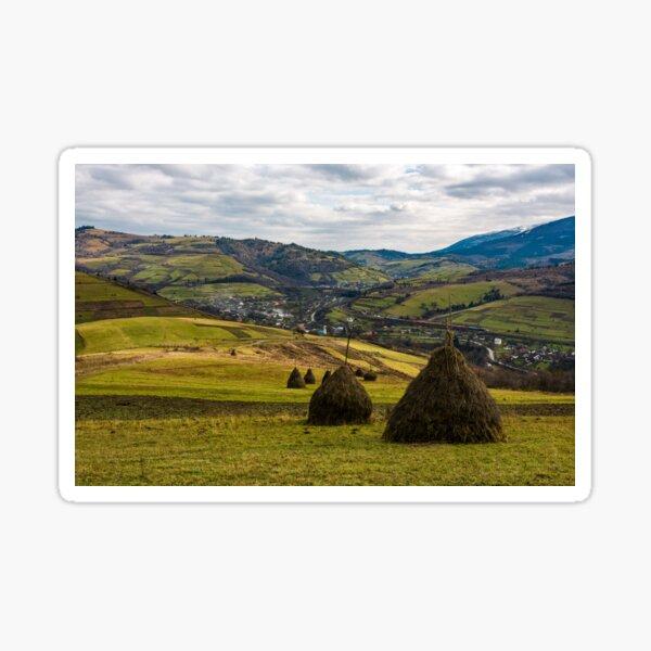 haystacks on grassy meadow in autumn mountains Sticker