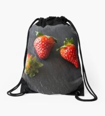 Three strawberries on a slate plate. Drawstring Bag