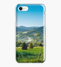 field with haystack on hillside in mountains iPhone Case/Skin