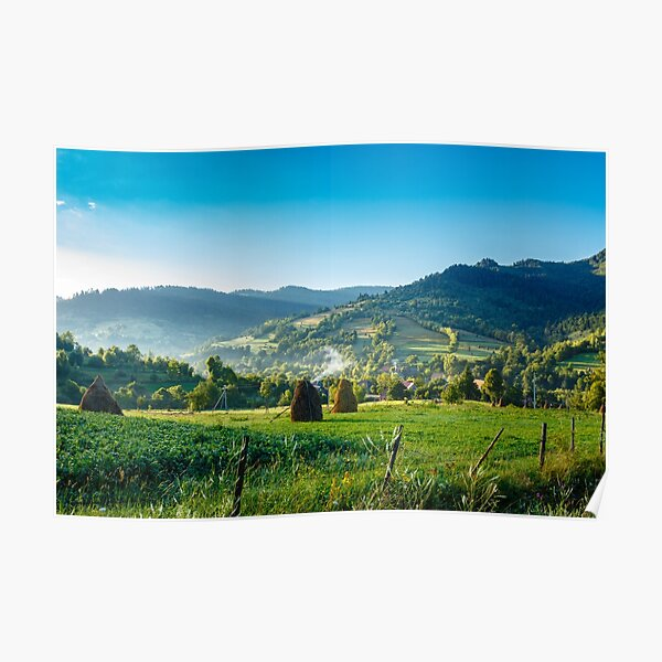 field with haystack on hillside in mountains Poster