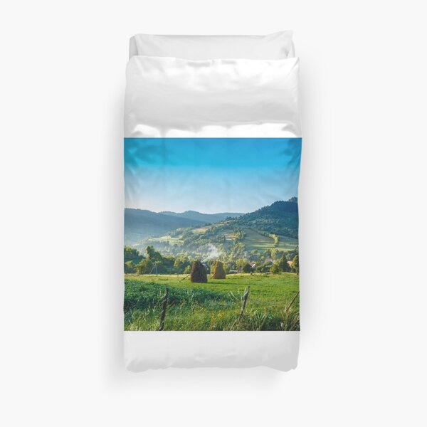 field with haystack on hillside in mountains Duvet Cover