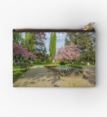 bench on the pavement in the park on a background of grass and sakura tree Studio Pouch