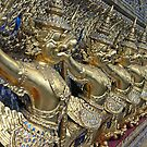 gold statues at a temple in Thailand by chord0