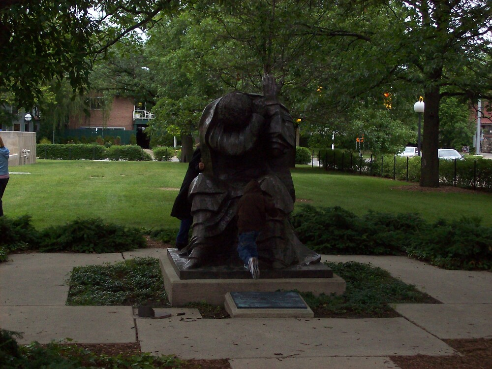 child kneeling before statue by ariyahjoseph