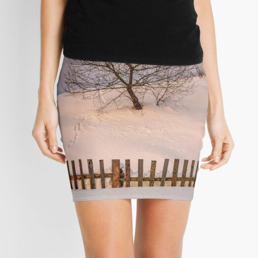 lonely  tree on snowy hillside behind the fence Mini Skirt