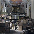 A US soldier stands amid crates and stacks of loot stored by Nazi Germany in Schlosskirche (Castle church), Bavaria, 1945. by Marina Amaral