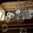 Glass ornaments in window by EplusC Studio
