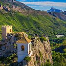 The bell tower and mountains at Guadalest by Ralph Goldsmith