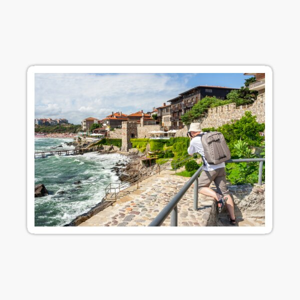 photographer with backpack shooting in old town Sozopol near sea in summer Sticker