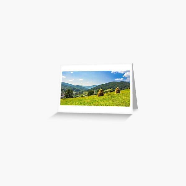 haystacks on hillside near the village Greeting Card