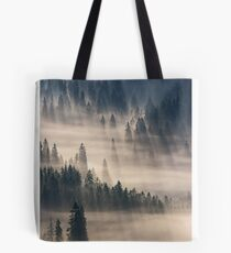 coniferous forest in foggy mountains Tote Bag