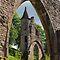 A Dilapidated Building Seen Through An Arch